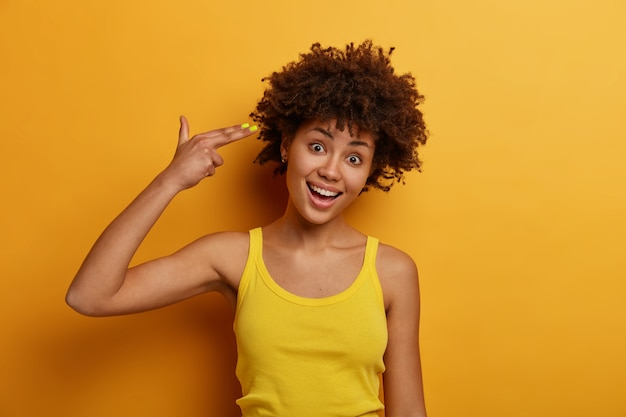 Funny joyful dark skinned woman commits suicide, makes finger gun pistol, tilts head and shoots in temple, foolishes around and feels bored, wears yellow casual clothes. people, lifestyle, emotions