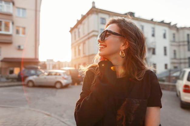 面白いうれしそうな女の子はオレンジ色の明るい太陽を楽しんでいます。幸せな日。