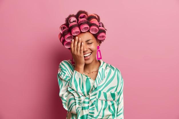 Смешная радостная женщина делает лицо ладонью, смеется над чем-то, носит бигуди, делает идеальную прическу, носит халат, позирует у розовой стены. женщины, уход и концепция домашнего стиля