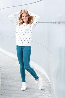 벽 근처 실내 재미 유행 흰색 운동화 빈티지 청바지에 흰색 스웨터에 재미 즐거운 젊은 여자
