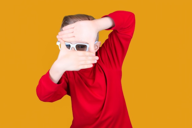 Funny kid in 3d movie glasses holds his hands together and looks through them