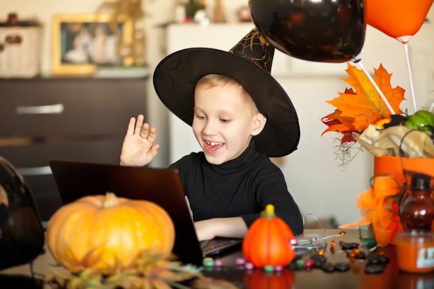 Забавный мальчик малыша в костюме ведьмы на хэллоуин, используя портативный компьютер цифрового планшета. онлайн-звонок друзьям или родителям.