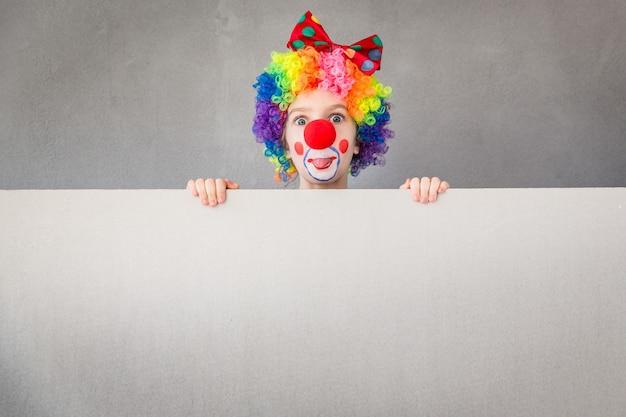 Забавный клоун ребенка. ребенок держит пустой знамя. концепция 1 апреля дурака