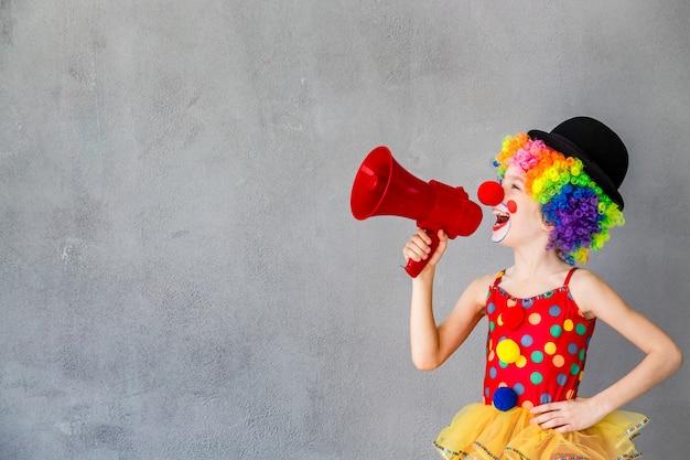 Забавный клоун ребенка. ребенок разговаривает с мегафоном. концепция 1 апреля дурака