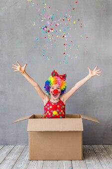 Забавный клоун ребенка в картонной коробке. ребенок играет дома. концепция 1 апреля дурака
