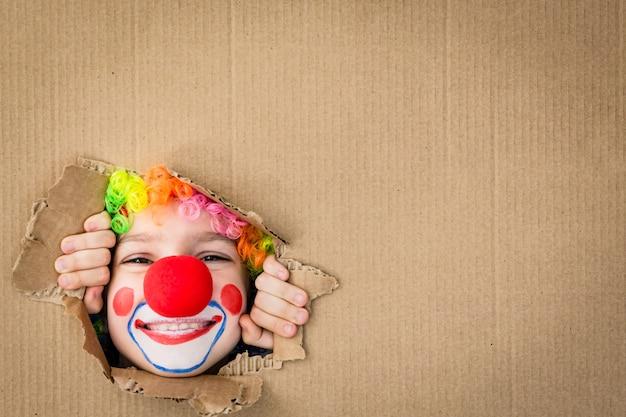 Забавный клоун ребенка, глядя через отверстие на картоне. ребенок играет дома. 1 апреля концепция дня дурака. скопируйте пространство.