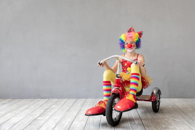 三輪車に乗って面白い子供のピエロ。家で遊んで幸せな子。エイプリルフールのコンセプト