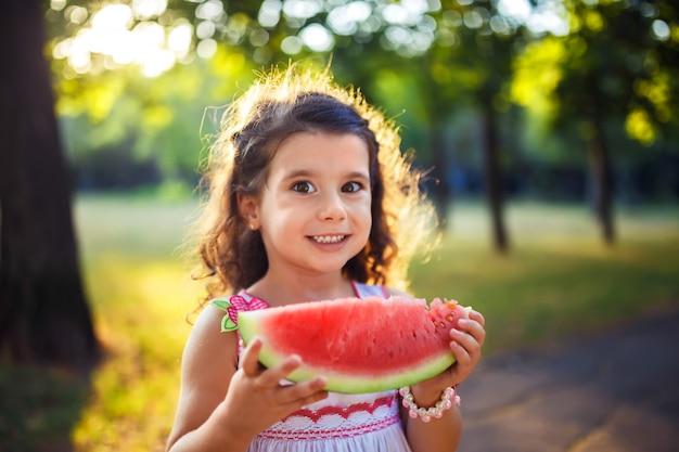Смешной малыш есть арбуз outdoors в парке лета, фокусе на глазах. ребенок, детка, здоровое питание.