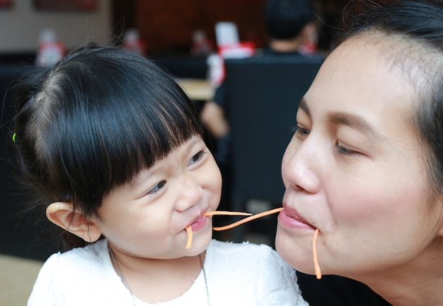 Funny kid girl eating carrot with mother.