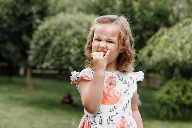 Смешная девочка ребенка ест бутерброд на открытом воздухе.