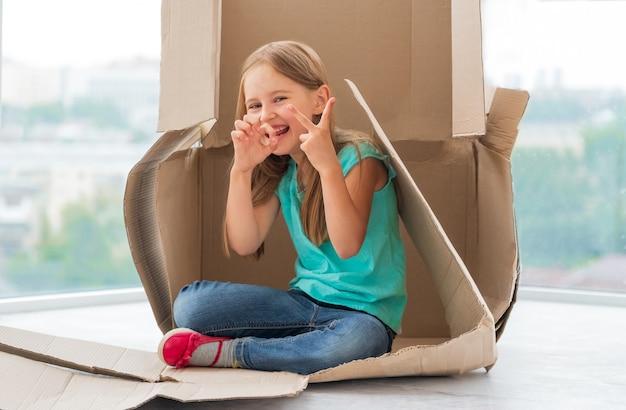 それをプレイハウスとして使用して段ボール箱に座ってジェスチャーをしている面白い子供の女の子