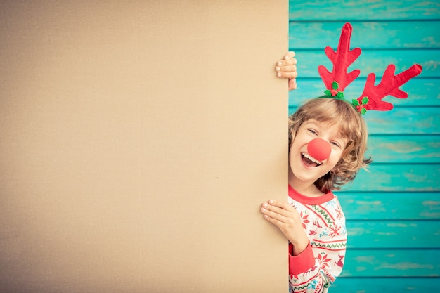 Funny kid holding cardboard banner blank child playing at home christmas holiday copy space