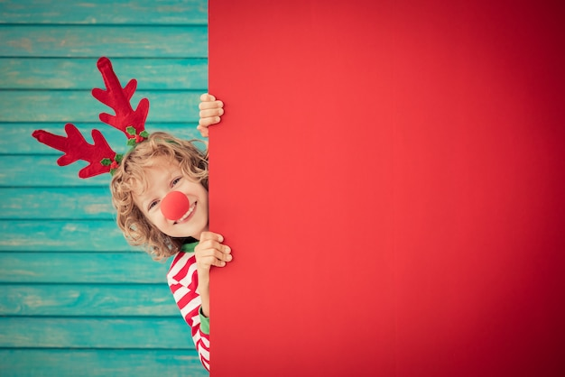 Funny kid holding cardboard banner blank child playing at home christmas holiday