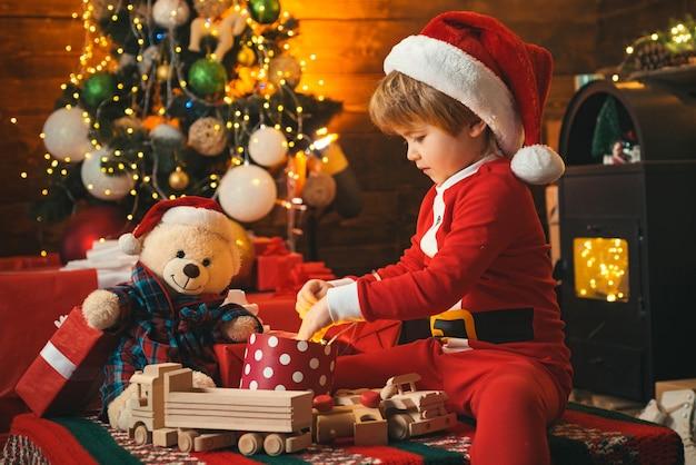 크리스마스 선물을 들고 재미있는 꼬마. 크리스마스 트리 근처 귀여운 작은 아이. 겨울 크리스마스 감정