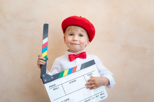 Забавный ребенок, держащий доску с хлопушкой. счастливый ребенок весело дома. концепция ретро кино