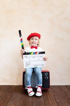 Funny kid holding clapper board. happy child having fun at home. retro cinema concept