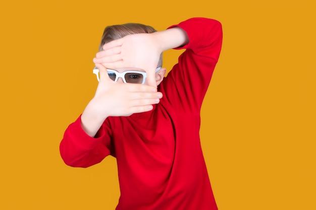 3d 영화 안경을 쓴 재미있는 아이가 두 손을 모아서 들여다본다