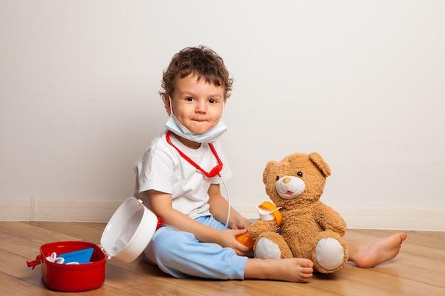 医療用マスクの面白い子供は医者でテディベアと遊ぶ。