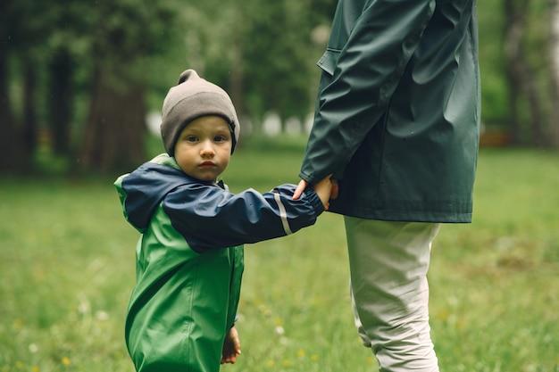 Забавный малыш в сапогах, играющих в парке дождя