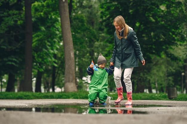 雨の公園で遊んで長靴で面白い子供