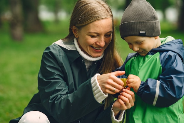 Забавный малыш в резиновых сапогах играет в дождевом парке