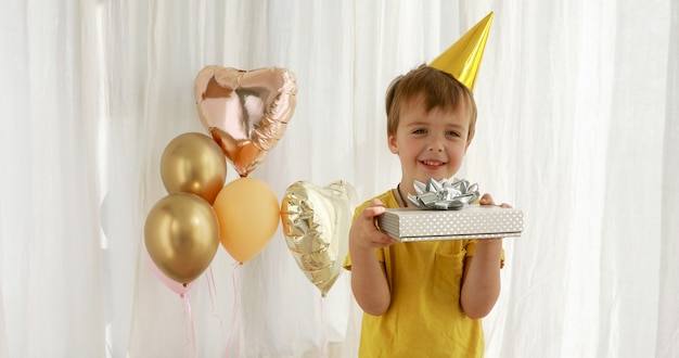 黄色のtシャツの面白い子供は紙のプレゼントボックスのクローズアップを保持します