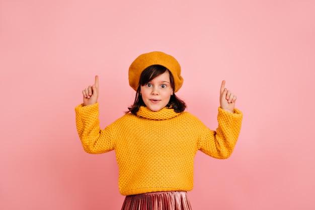 Ragazzo divertente. piccola ragazza francese in posa con le mani in alto sulla parete rosa.