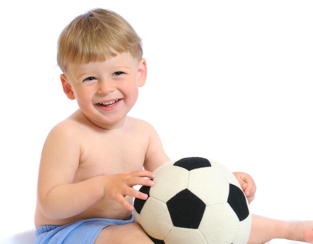 Забавный ребенок играет с футбольным мячом, изолированным на белом фоне. маленький мальчик в синих детских шортах