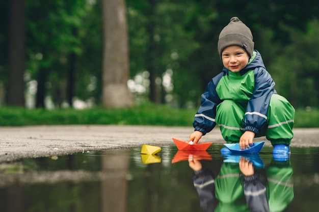 Funny kid in rain boots playing in a rain park