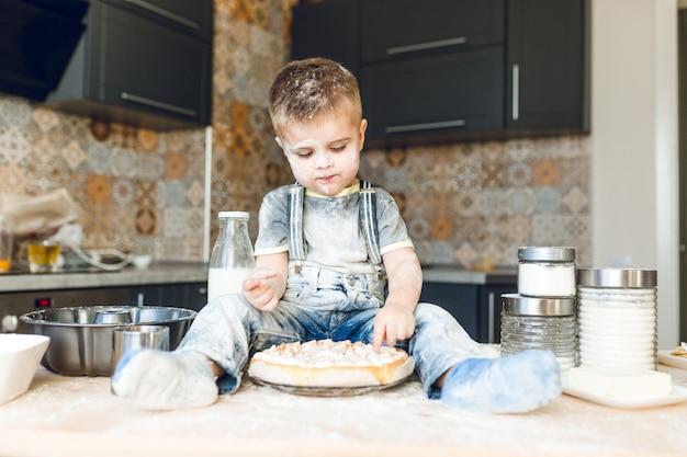 Bambino divertente che si siede sul tavolo della cucina in una cucina rustica che gioca con la farina e assaggia una torta.