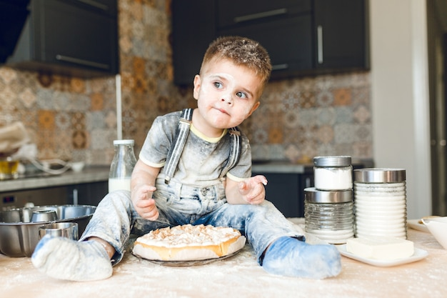 Funny kid sitting on the kitchen table in a roustic kitchen playing with flour and tasting a cake