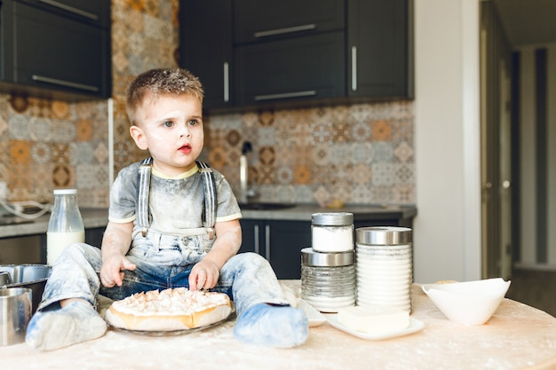 Funny kid sitting on the kitchen table in a roustic kitchen playing with flour and tasting a cake.