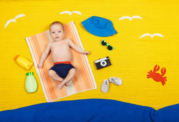 Funny kid in swimming trunks is lying on a towel, seagulls are flying over him