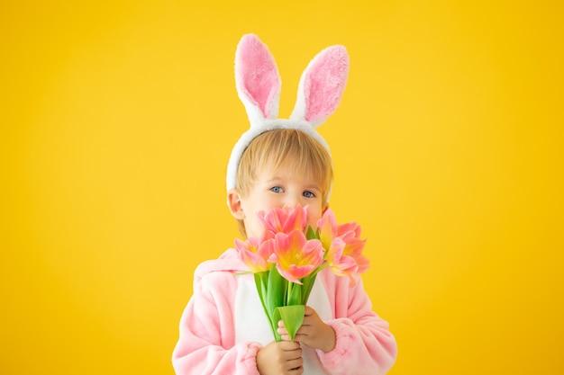 부활절 토끼 귀를 착용 하 고 노란색 벽에 튤립 꽃다발을 들고 재미있는 꼬마.