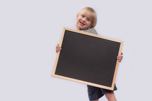 Funny kid with blackboard in his hands. copy space. template. mockup