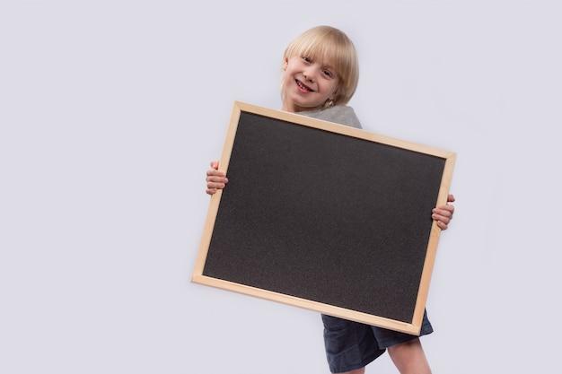 彼の手で黒板を持つ面白い子供。スペースをコピーします。テンプレート。モックアップ