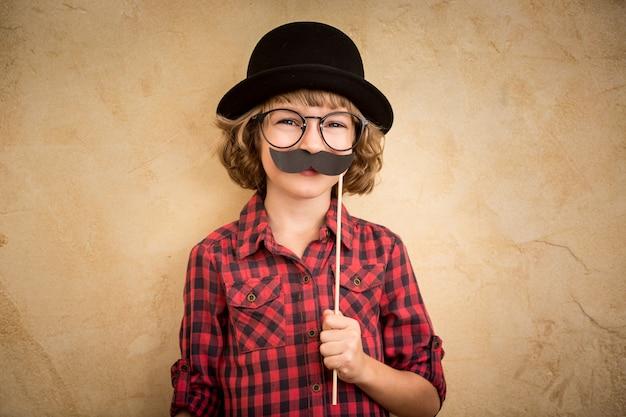 가짜 콧수염과 재미 있은 아이. 집에서 놀고 행복 한 아이