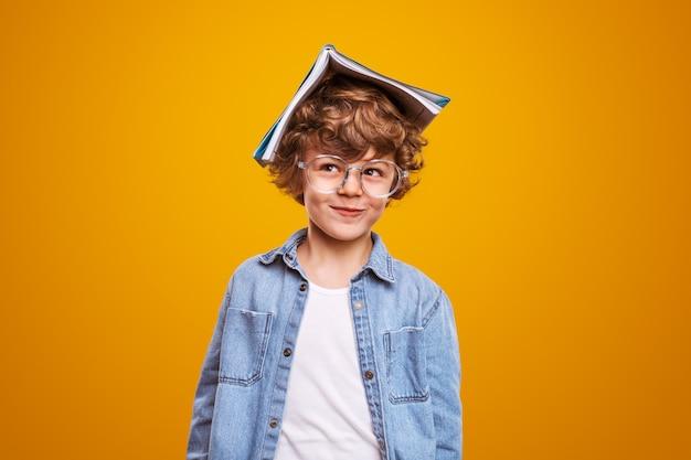 Забавный малыш с учебником на голове на желтом фоне