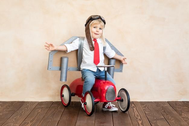 Забавный ребенок с игрушечным картонным реактивным пакетом