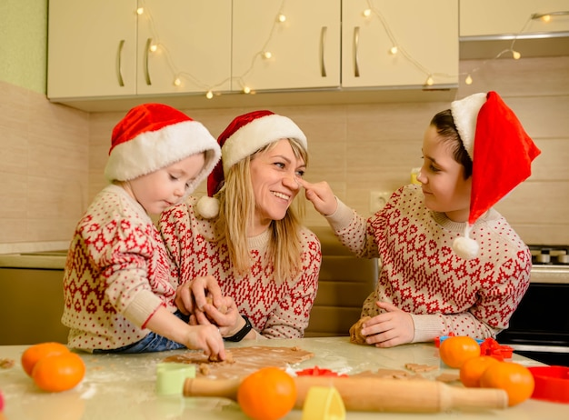 Веселые детки готовят тесто, пекут имбирные пряники на кухне в зимний день. веселые дети и мама пекут печенье на рождество.