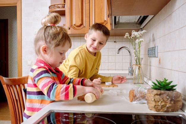 面白い子供たちは台所でクッキーを焼きます。幸せな家族。