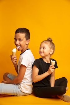 Funny kids eat vanilla ice cream in a waffle cone on a yellow background, joyful brother and sister