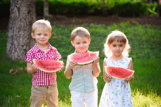 Funny kids eating watermelon outdoors in summer park.