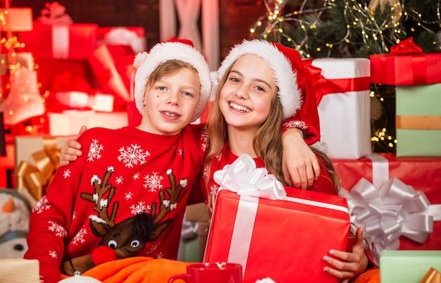 재미있는 아이들. 선물 가게. 아이 산타 모자 크리스마스 선물 상자. 메리 크리스마스. 겨울의 아름다움. 여가와 활동. 가족의 즐거움. 어린 행복한 소녀와 소년은 크리스마스 트리 근처에서 선물을 찾습니다.