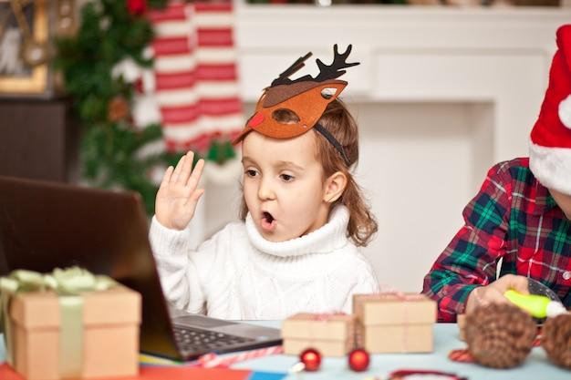 Забавные дети девочка и мальчик в кепке санты, используя портативный компьютер цифрового планшета. звоните через интернет друзьям или родителям и получайте удовольствие.