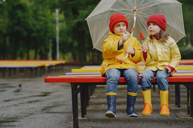 Веселые дети в дождевых сапогах играют в дождливом парке
