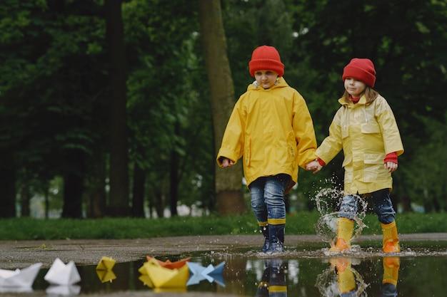 Смешные детки в резиновых сапогах играют с бумажным кораблем у лужи