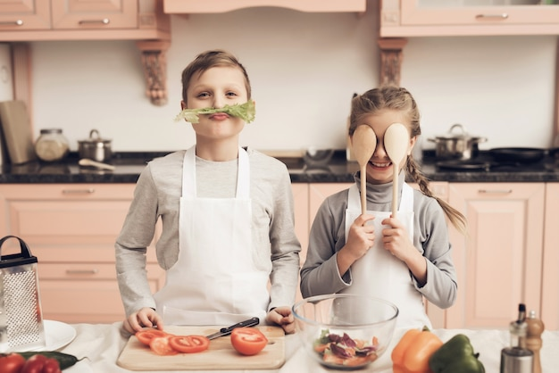 Funny kids play vegetables have fun at kitchen.