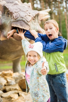 Funny kids playing in the adventure dino park. concept of happy childhood