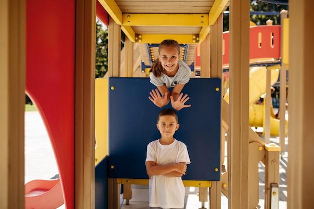Funny kids poses in rope park, playground. children climbing on suspension bridge